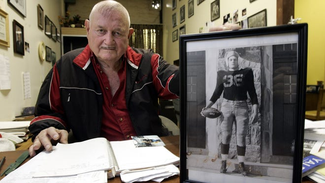 Dean Loucks, a former football star at White Plains High School and Yale, holds a photo of himself in uniform as a high school senior in 1952.