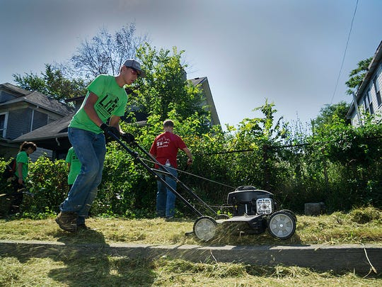 Tyler Rauhe cuts grass along the curb. He is a resident of Novi.