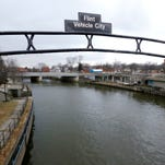 This Jan. 26, 2016, file photo shows a sign over the Flint River noting Flint, Mich., as Vehicle City. The U.S. Environmental Protection Agency says states are taking action to address the risk of lead in drinking water but more needs to be done to share key information with the public. In letters to state officials, Thursday, July 7, EPA urged states to post individual lead sampling results on public websites. That practice allows residents to see which homes and buildings have been tested and what level of lead was identified.