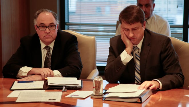 Hamilton County administrator Christian Sigman (left) and County Commissioner Chris Monzel, right, listen to city officials during an Enquirer editorial board meeting on Monday.