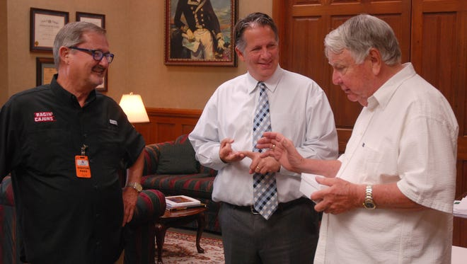 Gerald Guilbeaux, the conductor/music director of the Lafayette Concert Band, Lafayette Mayor-President Joel Robideaux and John R. Bourgeois have a chat in Robideaux's office after Bourgeois received a key to the city.