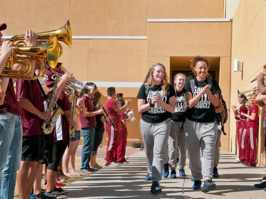 The NMSU women's basketball team walks through a column