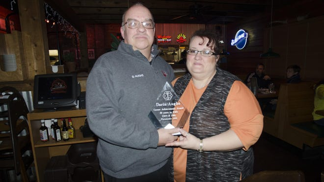 Darin Aughe poses for a photo with his wife and his career achievement award from Redline EMS during an award banquet at Texas Roadhouse on Dec. 29.