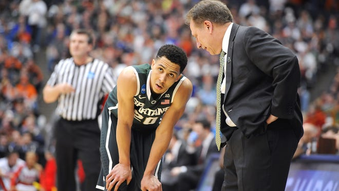 A hurting Travis Trice rests next to head coach Tom Izzo late in MSU's Elite Eight win over Louisville. Trice's incredible NCAA tournament run has MSU in the Final Four.