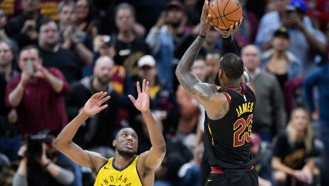 Cleveland Cavaliers forward LeBron James (23) makes a game-winning, three-point basket in the fourth quarter beside Indiana Pacers forward Thaddeus Young (21) in game five of the first round of the 2018 NBA Playoffs at Quicken Loans Arena.
