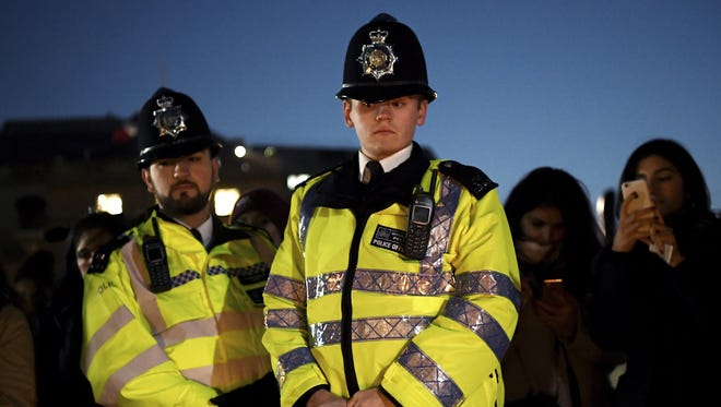 Two Metropolitan Police officers look on during a candlelit vigil at Trafalgar Square on March 23, 2017 in London.