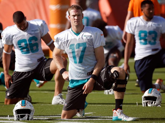 FILE - In this July 27, 2017, file photo, Miami Dolphins quarterback Ryan Tannehill (17) stretches with teammates during NFL football training camp in Davie, Fla. A person familiar with the decision says Tannehill will have surgery to repair the torn ACL in his left knee and will miss the entire season. The person confirmed the decision to The Associated Press on condition of anonymity Friday, Aug. 11, 2017, because the Dolphins had not disclosed it publicly. (AP Photo/Wilfredo Lee, File)