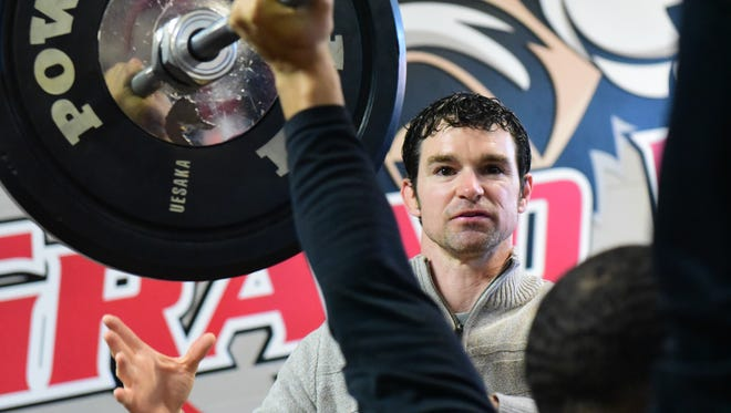 Zeb Sullivan watches the form of senior kinesiology student Jared Scruggs, 23, of Houston,  as he does an overhad press Friday, Jan. 29, 2016, at the Charles S. Johnson Wellness Center at Grand View University.