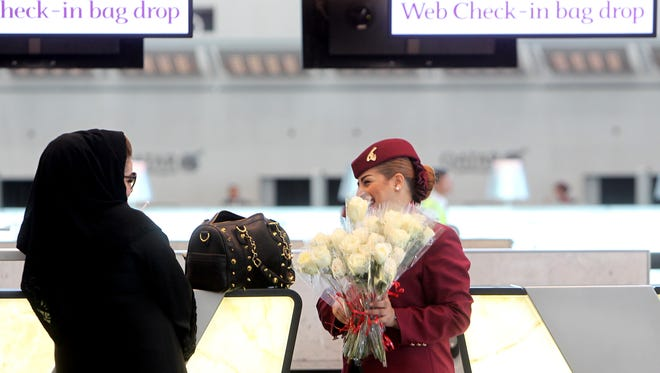 A Qatar Airways employee greets a Qatari passenger with flowers to help celebrate the airline's move to the new Hamad International Airport  in Doha, Qatar, on May 27, 2014.