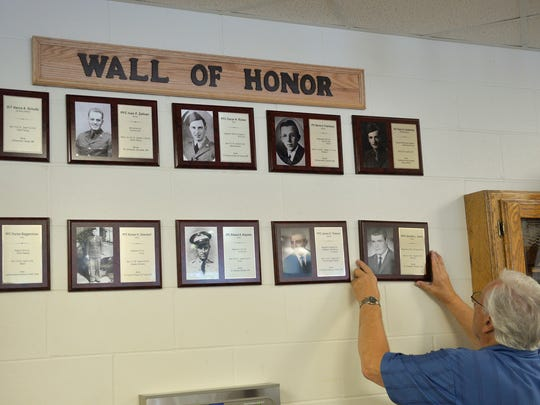 Avon resident Donald Kalis hangs a memorial plaque in honor of his brother, soldier Gerald Kalis, who died in the Vietnam War. The plaque was one of 10 hung Monday during a Memorial Day ceremony at Upsala High School.