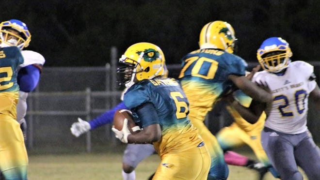 Estill High quarterback Angelo Lewis (6) carries the ball behind the blocking of Kavon Chisolm (70).