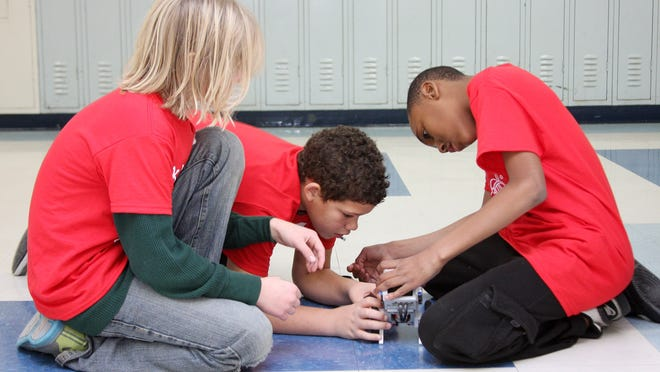 """Albion students Caleb Kiselica, Cameron Allen and Camonte Parker, all 11, test out their programming for an EV3, which they attempted to steer around the square hallways of Albion Community School during the recent """"Geekend"""" hosted by the Albion district."""