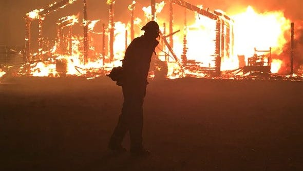 A firefighter can only watch as a structure burns Friday in the 1300 block of Fairview Road in the Goleta area. The Holiday Fire prompted mandatory evacuations.