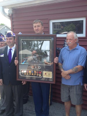 Zachariah Fike of Purple Hearts Reunited holds a plaque honoring Army Spec. Emi lio Ricci of New Haven, Conn., at VFW Post 5913. At right is Ricci's nephew, Dav id Ricci, accepting his uncle's Purple Heart. At left: Richard Gerbeth Jr. of Wappingers Falls.