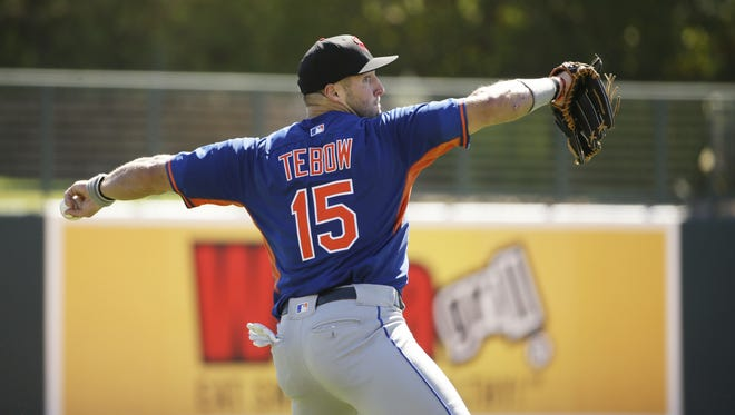 Tim Tebow warms up before his fall league debut on Tuesday in Glendale.