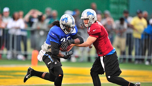 Matthew Stafford hands off to Wayne State alum Joique Bell during the Lions' open practice at Wayne State on July 30, 2014.