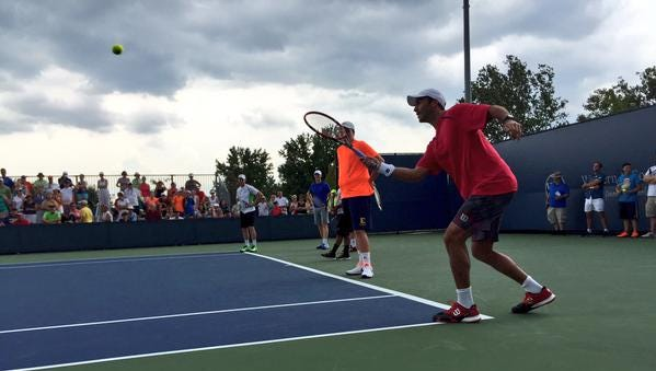 Romanian tennis player Horia Tecau volleys a shot across the court to a fan during the ATP Doubles Showdown event Monday at the Western & Southern Open.