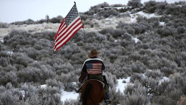 BURNS, OR - JANUARY 07:  Dwayne Ehmer carries an American flag as he rides his horse on the Malheur National Wildlife Refuge  on January 7, 2016 near Burns, Oregon.  An armed anti-government militia group continues to occupy the Malheur National Wildlife Headquarters as they protest the jailing of two ranchers for arson.  (Photo by Justin Sullivan/Getty Images) *** BESTPIX ***