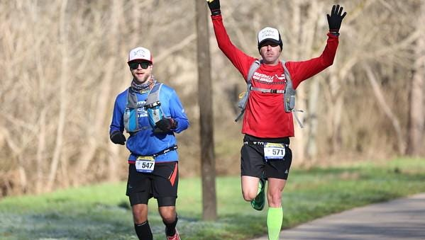 Feeling pumped up as they continued on the 100-mile Pistol Ultra Run in early January are Canton's Jason Jones (left) and Dan McGuire.