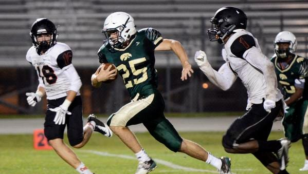 Viera's Mike Vega is brought down by Todd Powers (1) and Cody Franc0 (18) of Spruce Creek after a big first down run in Wednesday's spring game at Viera High School.