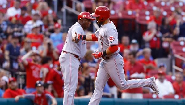 Cincinnati Reds' Eugenio Suarez, right, is congratulated by third base coach Billy Hatcher after hitting a home run off of St. Louis Cardinals starting pitcher Jaime Garcia during the fourth inning of a baseball game, Wednesday, Aug. 10, 2016, in St. Louis.