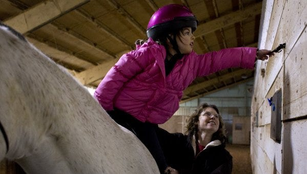 Charlotte Bradley of Ferdinand, 6, reached for a miniature horse figure that Hippotherapist Carrie Smith had hidden in the barn during the child's hippotherapy lesson Thursday at Freedom Reins Therapeutic Riding Center in Jasper. Bradley has a genetic disorder called Prader-Willi syndrome, which includes symptoms like weak muscles and delayed development. Bradley began sessions with Smith last year as a way to improve coordination, balance and strength.