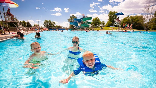 A trio of Great Falls swimmers enjoy a soak at Mitchell Pool in Great Falls. City officials will consider minor increases to pool admission fees at the Feb. 20  meeting of the Great Falls City Commission