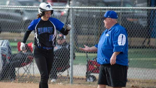 Oshkosh West's Brianna Davis slap hands with her first-base coach after a base hit Thursday at Oshkosh West High School.