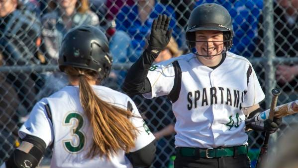 Oshkosh North's Sophie Averkamp smiles as Libby Neveau runs the bases on a home run May 17.