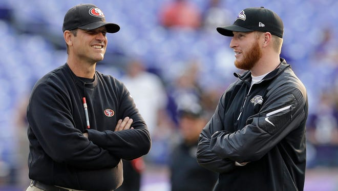 Then-San Francisco 49ers head coach Jim Harbaugh, left, chats with his son Jay, a then-Baltimore Ravens offensive assistant, before an NFL preseason football game on Aug. 7, 2014. Jay will be the tight ends coach under Jim at Michigan, according to a report.