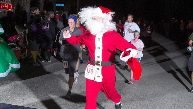 A fit and slim-downed Santa Claus makes his way over the finish line of the 2015 Jingle Bell 2-Miler in Satellite Beach.