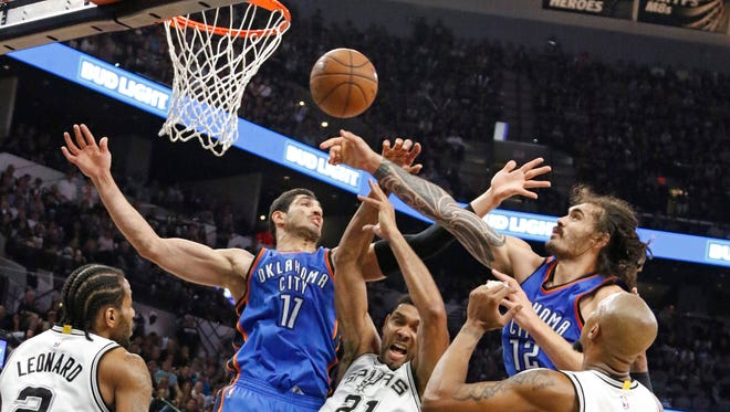 Tim Duncan #21 of the San Antonio Spurs battles Enes Kanter #11 and Steven Adams #12 of the Oklahoma City Thunder for a rebound in game Five of the Western Conference Semifinals during the 2016 NBA Playoffs at AT&T Center on May 10, 2016 in San Antonio, Texas.