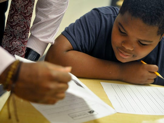 Dakeoe Fletcher, 13, of Wilmington, gets help from his teacher, Ronald Shaw, of New Castle, while completing an English pre-test at Bayard Middle School in Wilmington Wednesday, September 14, 2016.  The usual annual turnover at Bayard is approximately 30 percent, and in the 2015-16 school year, it was more than 60 percent, according to a lawsuit filed by the ACLU.