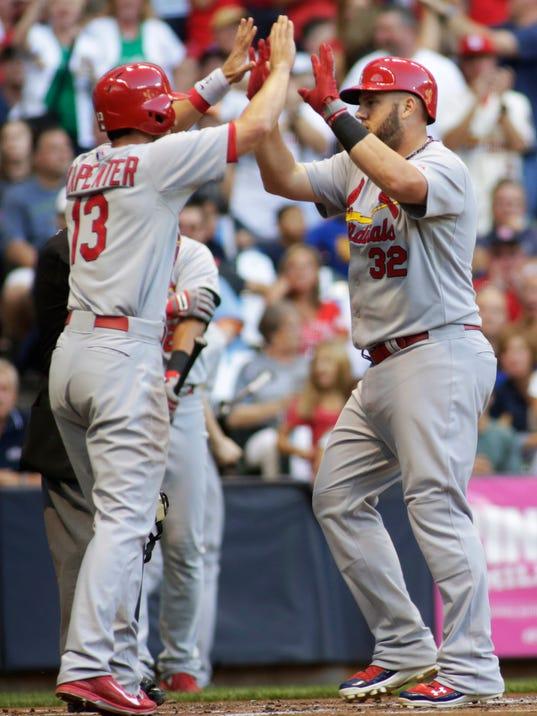 St. Louis Cardinals' Matt Adams, right, celebrates his two-run home run against the Milwaukee Brewers with Matt Carpenter, left, during the first inning of a baseball game Saturday, Sept. 6, 2014, in Milwaukee. (AP Photo/Darren Hauck)