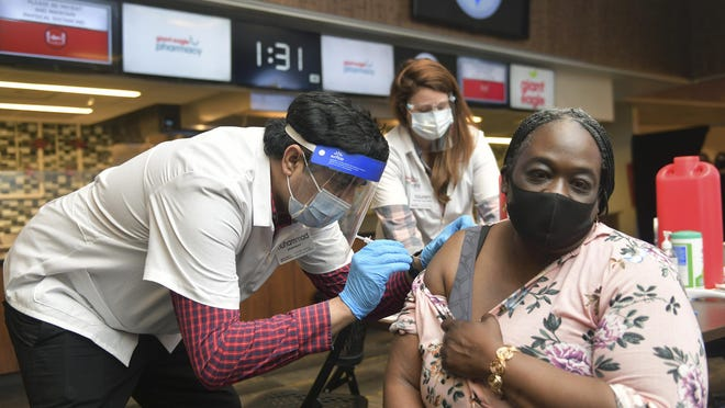 Dena Langston, a prekindergarten teacher at the Homewood-Brushton YWCA, receives a COVID-19 vaccination from Muhammad Cheema, a pharmacist with Giant Eagle supermarket chain, at Heinz Field in Pittsburgh on Thursday.