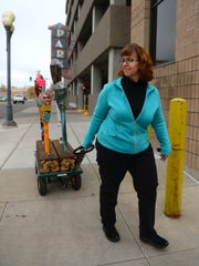 Joan Redeen of the Great Falls Business Improvement District pulls four painted parking meters by the 4th Street North parking structure. Joan uses these meters as an example of a project she is working on to decorate decomissioned analogue meters that will be planted in front of the 4th Street structure as an interactive art installation.  The money collected in the meters with help fund future art projects downtown.