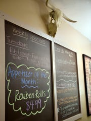 A cow skull adorns the weekly specials board at Corner Stables Thursday, March 10, 2016, in York Township. Corner Stables, which has an 18-and-over bar as well as a family-friendly restaurant, features ribs, broasted chicken and more.