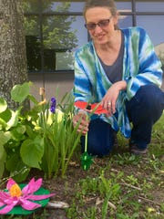 Three-dimensional art teacher Mimi Hoffman shows some of the flowers her students made out of recycled milk cartons for the West Bloomfield High School Literary Garden.
