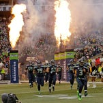 Fire effects go off as Seattle Seahawks players, including quarterback Russell Wilson (3), run out of the tunnel before an NFL football game against the Cleveland Browns, Sunday, Dec. 20, 2015, in Seattle.