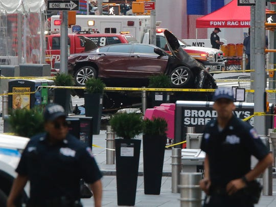 Police officers secure the area near a car after it plunged into pedestrians in Times Square in New York on May 18, 2017.