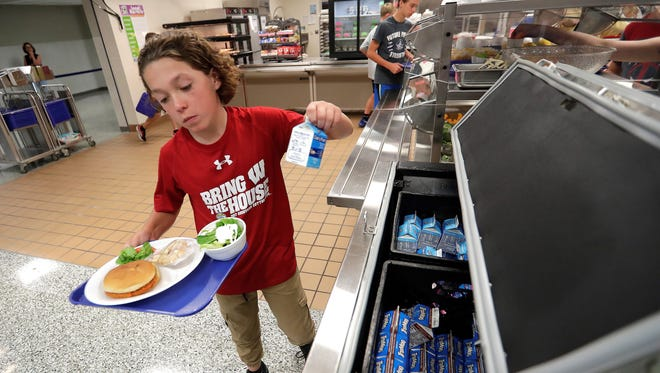 Student Luke LaFond picks up a salad Tuesday from the salad bar as he goes through the lunch line at Bay View Middle School in Howard.