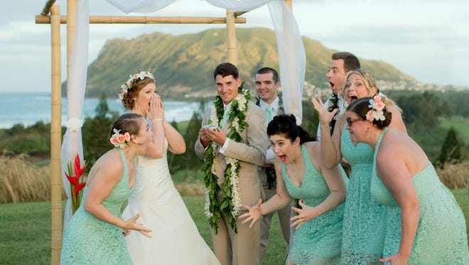 Natalie Heimel (second from left) and Edward Mallue Jr. (third from left), both U.S. Army captains stationed in Hawaii, react with their wedding party after getting a phone call from President Obama during their ceremony at Kaneohe Klipper Golf Course in Kaneohe Bay, Hawaii.