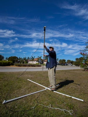 Joe Huie, 87, sets up his Ham radio antenna in an open field near his south Cape Coral home Tuesday, January 30. Huie, a member of the Fort Myers Amateur Radio Club (FMARC), has written a book on the topic.
