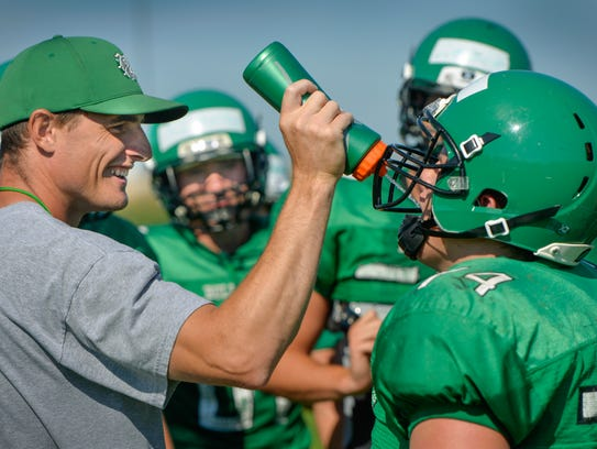 Paynesville head coach Max Meagher, left, squirts water