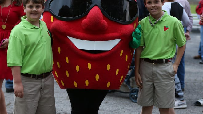 Sawyer Hunley and Mills Terry escort The Berry, mascot of the West Tennessee Strawberry Festival, at the opening ceremony Monday night.