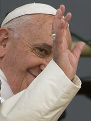Pope Francis waves on a balcony after his address to