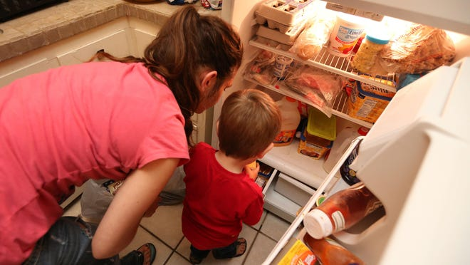 A Springfield woman and her 2-year-old son put away groceries in this 2015 News-Leader photo. She had recently moved into an apartment from the Missouri Hotel and relied on welfare benefits including TANF and WIC to provide for her two young children.
