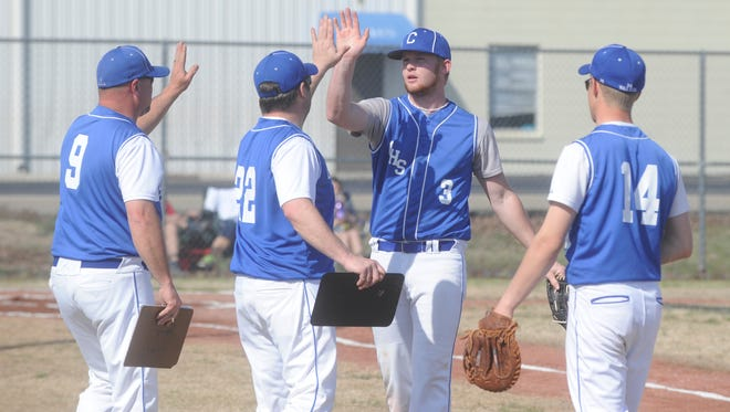 Cotter pitcher Ryan Roberts (3) high-fives head coach Marty Hall (9) and assistant coach Dwayne Adams (22) during a recent game against Green Forest.