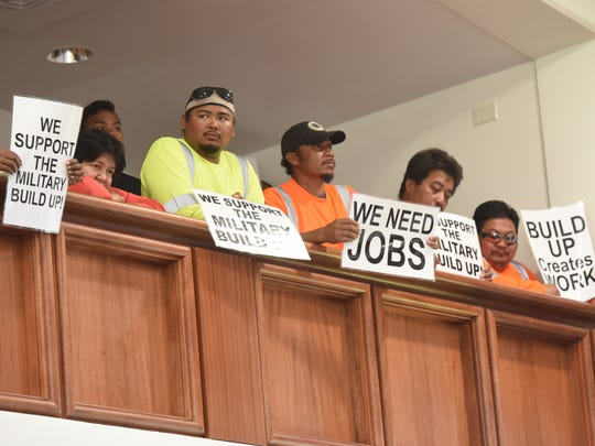 A group of workers display signs expressing their support for Legislative Resolution 294 during a public hearing at the Guam Congress  Building in Hagåtña on Wednesday, Nov. 22, 2017. The hearing was held to gather input from the public on the resolution, introduced by Sen. Michael San Nicolas, to support the buildup by the military on Guam.