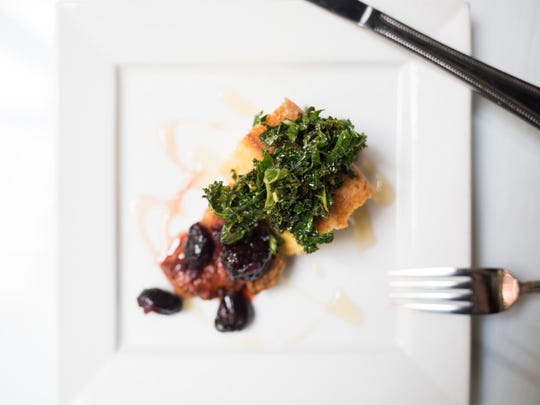 Pictured is a cold smoked and deep fried quail breast, topped with black cherry chutney and apple cider gastrique, wilted kale, and sweet potato cornbread.